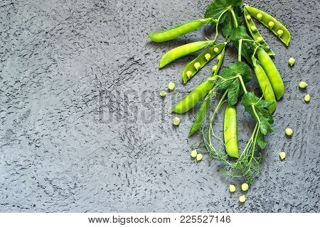 Branch Of Fresh Green Peas With Pods And Leaves On Gray Textured Background. New Harvest Of Organic
