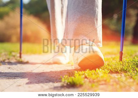 Rest And Peace. Close Up Of Elderly Woman Using Crutches While Having Splendid Walk Through The Park