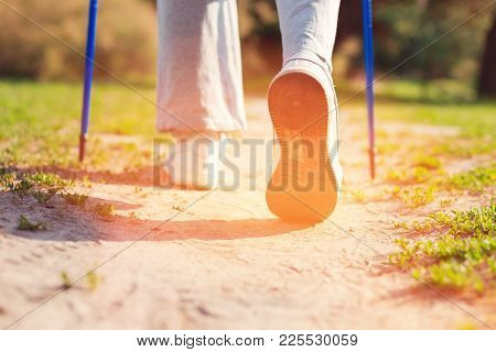 Pleasant Mood. Close Up Of Old Woman Using Crutches While Walking Through The Forest