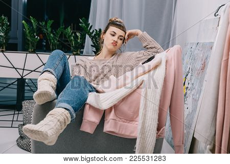 Girl Sitting On Armchair And Skeptically Looking At Sweaters On Hangers