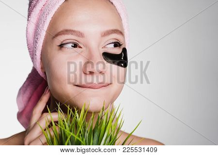 Happy Woman With A Towel On Her Head Put Patches Under Her Eyes And Looks Away