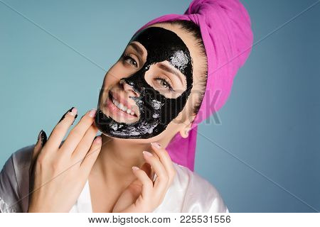Happy Woman With A Towel On Her Head Applied A Cleansing Mask On The Face Skin