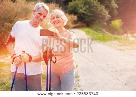 Bright Photos. Elderly Family Standing In Front Of You While Holding A Mobile Phone And Admiring Pho