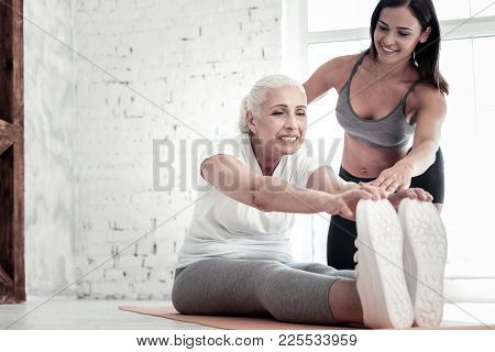 Healthier Than Yesterday. Beautiful Retired Woman Smiling While Listening To Her Female Coach And St