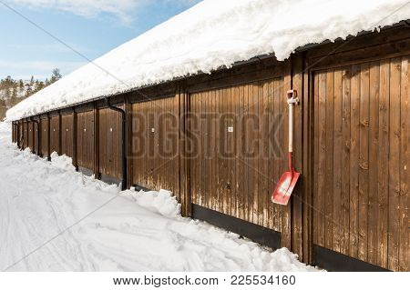 Brown Multiple Garage Building For Snowmobiles, Snow On The Ground, Shovel On The Garage Wall, And W