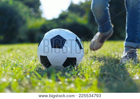 Favorite Leisure Activity. Scaled Up Look On A Ball Lying On A Football Field With A Man Wearing Cas