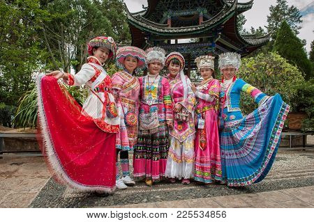 Dancing In Lijiang City. Girls In National Costumes Of China Dance At The Town Hall