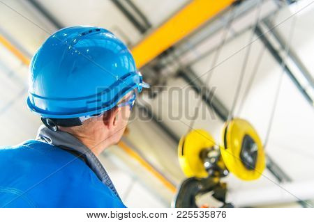 Caucasian Production Line Technician In Blue Hard Hat Checking On The Overhead Warehouse Crane Insta
