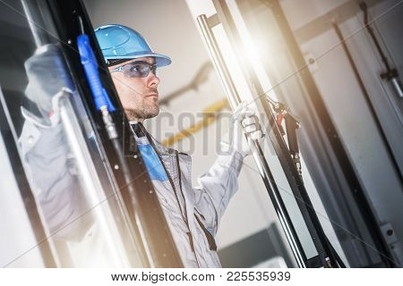 Caucasian Cnc Technician Taking Look Inside The Modern Cnc Machine. Metalworking Industry Concept.