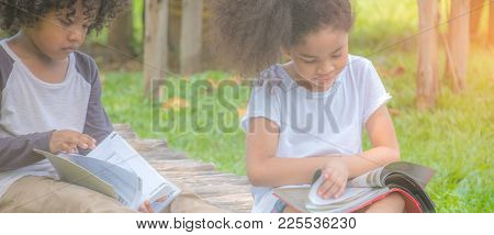 Kids Reading A Book In Summer Garden. Children Study. Boy And Girl Play In Yard. Playing And Learnin