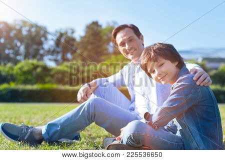 Supportive Relations. Selective Focus On A Positive Minded Teenager Sitting Next To His Loving Fathe