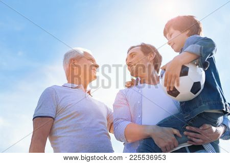 Men Day. Low Angle Shot Of A Cheerful Father Holding His Adorable Son In Arms While Enjoying A Pleas