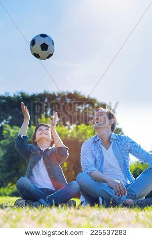 Having So Much Fun Together. Excited Father And Son Sitting In The Grass And Grinning Broadly While