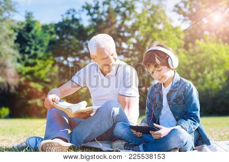 Only Men Day. Positive Minded Senior Man With A Book Looking At His Smiling Preteen Grandson While T