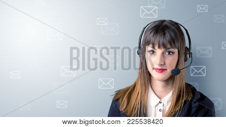 Young female telemarketer with white envelopes surrounding her