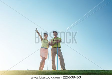 Low-angle view of the silhouette of a man pointing to the horizon, while standing next to his female partner on a professional golf course against sunshine and clear blue sky