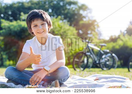 Having So Much Time. Cute Male Youngster In Casual Sitting In The Grass And Grinning Broadly While S