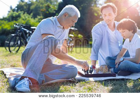 Imparting Knowledge. Pensive Family Reuniting At A Chessboard While Spending Their Leisure Time Outd