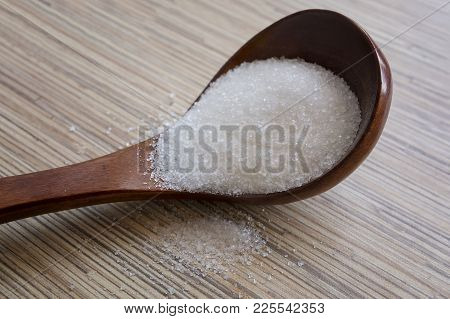 Wooden Spoon With White Sugar On Wooden Background