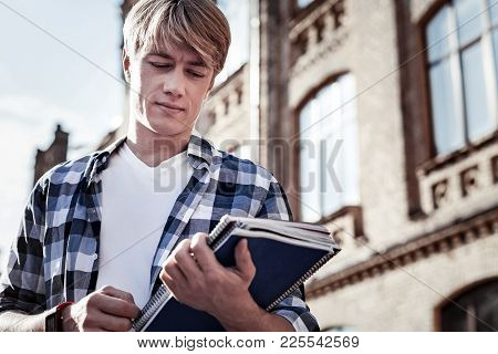 College Student. Nice Serious Smart Man Holding His Books And Looking At Them While Being A College