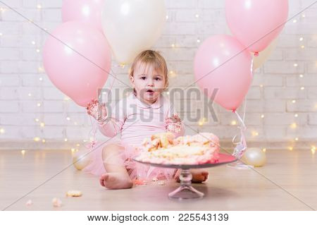 First Birthday Celebration - Funny Little Girl With Smashed Cake Over Brick Wall Background With Lig
