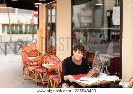 Aged Female Screenwriter Sitting In Outdoor Cafe And Reproduce Scenario From Paper Drafts In Text Fi