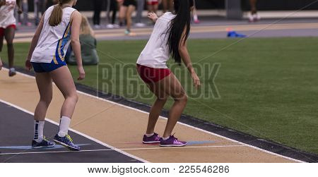 Two High School Girls Are Ready To Exchange The Baton With Their Teammates During A Relay Race Indoo