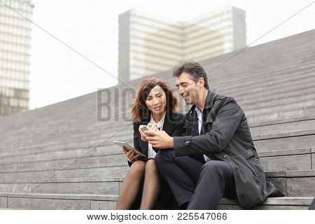 Married American Business Couple Use Tablet And Smartphone, Middle-aged Teachers Planning Summer Hol