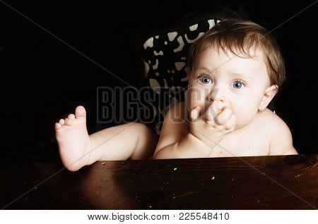 Feeding A Child. Funnybaby At Meal Eating A Bread Crust. Close-up Photo On Black Background. Copy Sp
