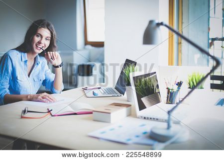 Young woman sitting at office table with laptop. Young woman. Laptop