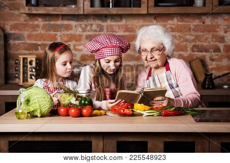 Granny with two granddaughters reading recipe from cooking book and cooking salad