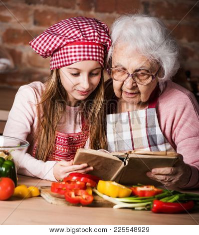 Little granddaughter reading recipe book with her granny sitting at kitchen