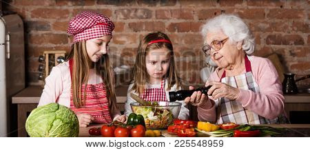 Two cute little sisters help her granny to prepare vegetable salad at kitchen at home