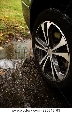 Detail Of Car Wheel. It Is Standing  Beside The Puddle.car Wheel Is Standing Beside The Puddle  In T