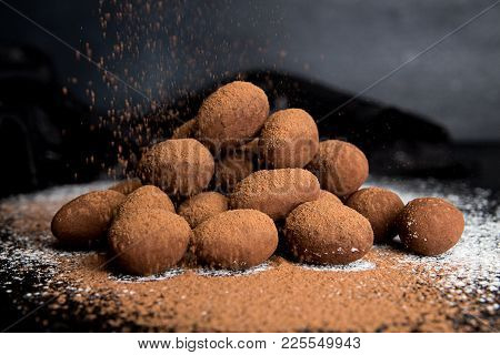Candies Almonds Coated In Chocolate Cocoa Paste On Dark Black Background. Cocoa Powder Strewing On S