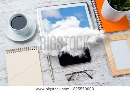 Top View Of Modern Workplace With Office Stuff And Cloud Above Presenting Still Office Life. Mixed M