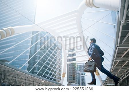 Young Businessman With A Briefcase Running Fast In A City Street On A Background Rush Hour