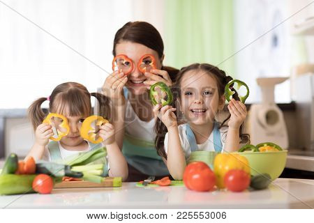 Happy Family Mom And Kids Having Fun With Food Vegetables At Kitchen Holds Pepper Before Their Eyes