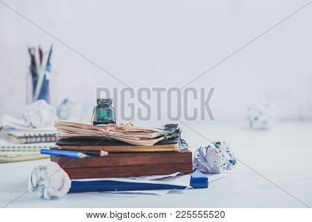 Header With Writer Workplace. Inkwell On A Stack Of Drafts, Pencil Boxes And Papers. High Key Still