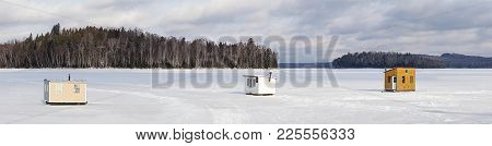 Panorama Of Small Wooden Shelters For Ice Fishing Installed On A Frozen Lake With Trees And Sky In T
