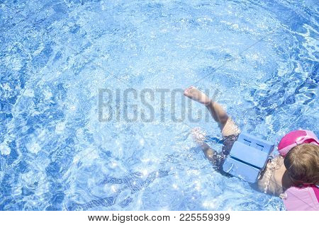 Little Boy Enjoying Safety At Swimming Pool. He Wears Armband Floats And Float Belt