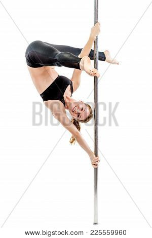 Flexible Trainer In Tights And Top Performs Gymnastics On A Pylon On A White Background
