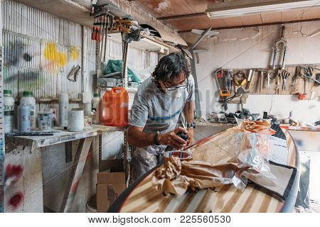 Man Repairing And Painting Surfboard