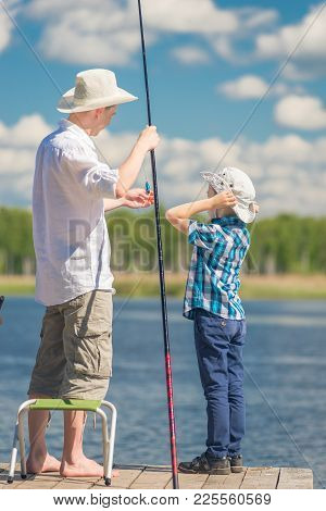 7-year-old Son Helps His Father To Fish In The Lake