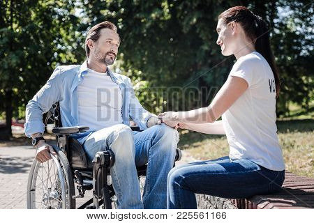 Sympathy And Support. Positive Nice Young Woman Looking At The Disabled Man And Holding His Hand Whi
