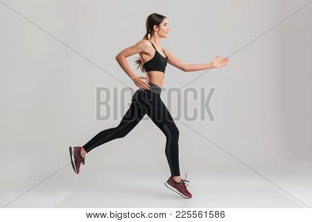 Profile picture of energetic caucasian female in sportswear running isolated along gray background