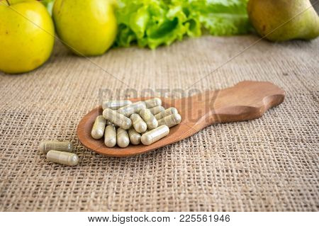 Synthetic Or Natural Vitamins. Veggie Capsules In Brown Wooden Spoon On A Background Of Green Fruits