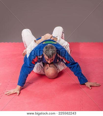 Brazilian Jiu-jitsu Instructor In Traditional Kimono Show Ground Mount Position