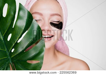 Happy Woman With Closed Eyes With A Towel On Her Head Applied Patches Under The Eyes