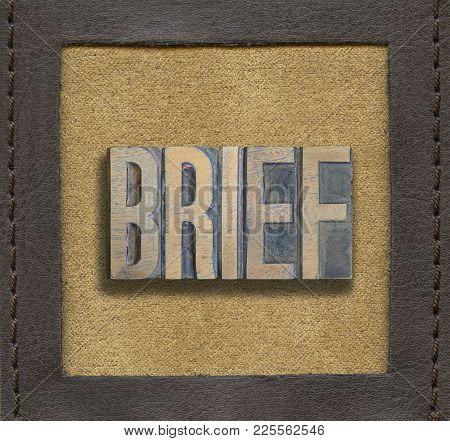 Brief Word Assembled From Vintage Wooden Letterpress Inside Stitched Leather Frame